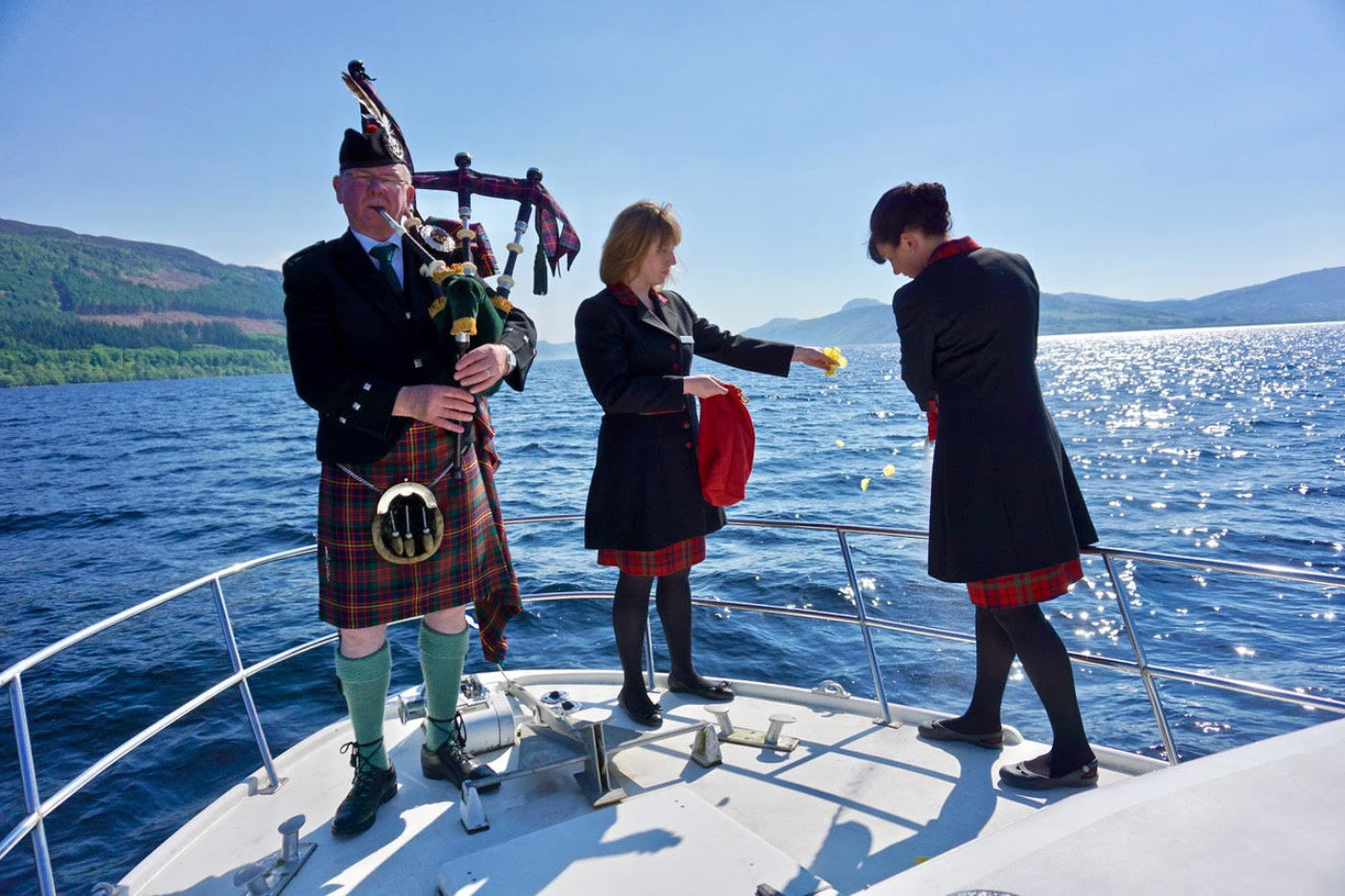 Piper Donald Shaw played 'Dark Island' as John Fraser & Son Directors Vicki Fraser (left) and Sarah Maclean (right) scattered the ashes of the late Alan Heaton onto the waters of Loch Ness. Yellow rose petals were also scattered as a symbol of new beginnings.
